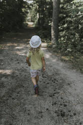 Rear view of girl walking on a forest path - DWF00460