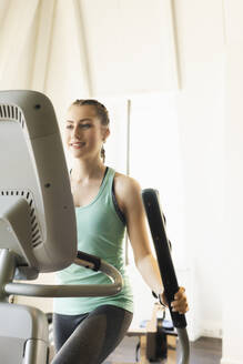 Young woman exercising on step machine in fitness gym - SEBF00131