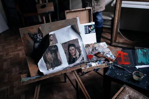 Deutschland, Bonn, im Studio einer Künstlerin, Staffelei mit BIldern von der Malerin und Farben - OGF00090