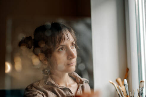 Portrait of a female artist in her studio looking out of window - OGF00099