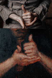 Close-up of hands of a female painter in her studio with a painting of hands - OGF00102