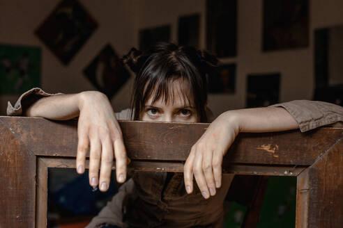 Deutschland, Bonn, im Studio einer Künstlerin, Portrait einer Künstlerin mit dem Bilderrahmen - OGF00105