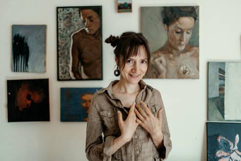 Deutschland, Bonn, im Studio einer Künstlerin, Portrait einer Künstlerin mit ihren Bildern im Hintergrund - OGF00108