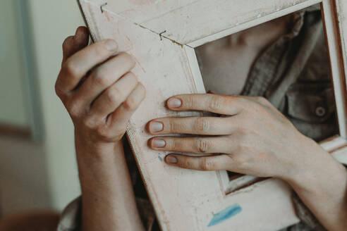 Deutschland, Bonn, im Studio einer Künstlerin, Portrait einer Künstlerin mit Bilderrahmen, nur Hände - OGF00111
