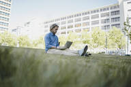Young man sitting on a meadow using laptop - KNSF06157