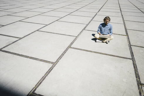 Young man sitting on a square using laptop - KNSF06178