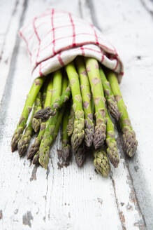 Close-up of green asparagus in napkin on wooden table - LVF08233