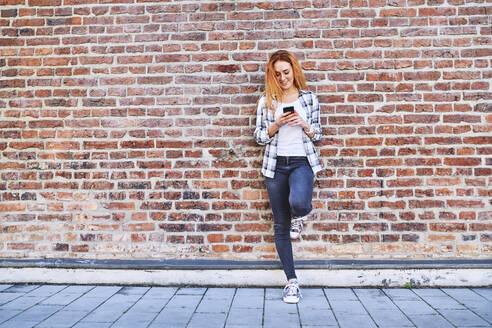 Young woman leaning against brick wall in the city while using smartphone - BSZF01316