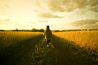 Mixed race child walking on path through rural field - BLEF13461