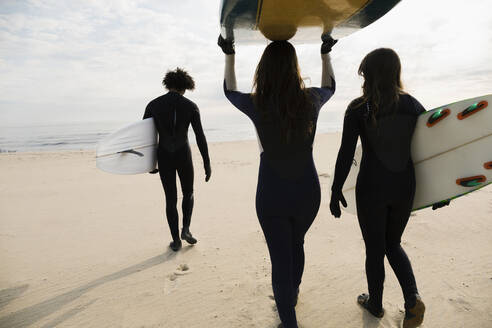 Surfers carrying boards on beach - BLEF13614