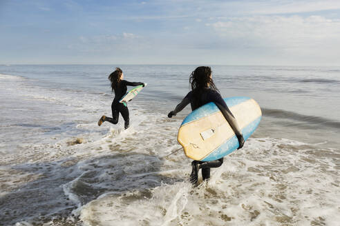 Surfers carrying boards in waves - BLEF13617