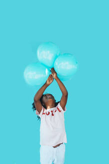 Little afro girl In front of a blue wall and holding balloons - JCMF00083