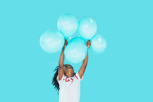 Little girl In front of a blue wall, holding balloons - JCMF00086