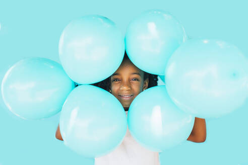 Little girl In front of a blue wall, holding balloons - JCMF00089