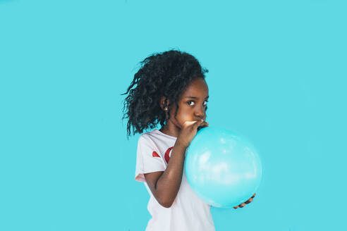 Little girl In front of a blue wall, blowing up balloon - JCMF00092