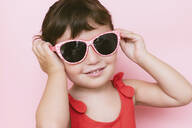 Portrait of smiling little girl wearing sunglasses against pink background - GEMF03035