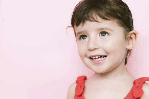 Portrait of smiling little girl in front of pink background looking up - GEMF03041