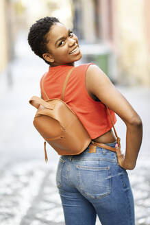 Portrait of smiling young woman with light brown leather backpack - JSMF01199