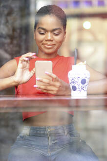 Portrait of smiling young woman in a bar looking at cell phone - JSMF01205
