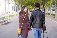 Tourists Couple holding hands and walking down the street with a wheel suitcase, Barcelona, Spain - GEMF03048
