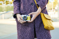 Close-up of woman holding a vintage analog camera - GEMF03078