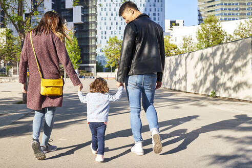Parents and little girl holding hands and walking together in Barcelona, Spain - GEMF03087
