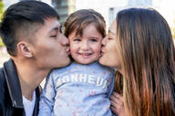 Happy parents kissing little girl - GEMF03096