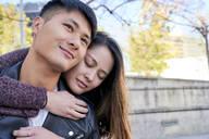 Happy young woman hugging boyfriend outdoors - GEMF03099