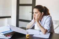 Frustrated female student with documents at desk at home - LJF00590
