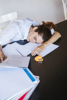 Exhausted female student lying on desk at home with documents - LJF00593