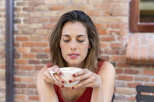 Portrait of young woman sitting at street cafe with cup of coffee - AFVF03628