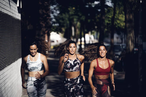 Front view of three women running through the streets of Madrid Spain. - OCMF00543