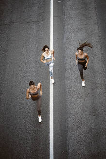 Top view of three sporty young women running on a street - OCMF00549