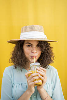 Portrait of woman with straw hat, drinking juice, yellow background - AFVF03663