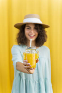 Portrait of woman with straw hat, drinking juice, yellow background - AFVF03666