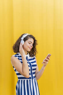 Portrait of young woman with headphones using smartphone - AFVF03672