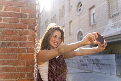 Young woman leaning on brick wall, taking a selfie - AFVF03708