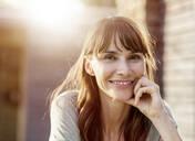 Portrait of smiling brunette woman in backlight - FMKF05775