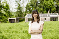 Portrait of confident woman standing on meadow in front of a house - FMKF05787