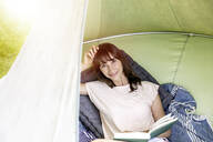 Portrait of smiling woman reading book in a hanging tent - FMKF05793