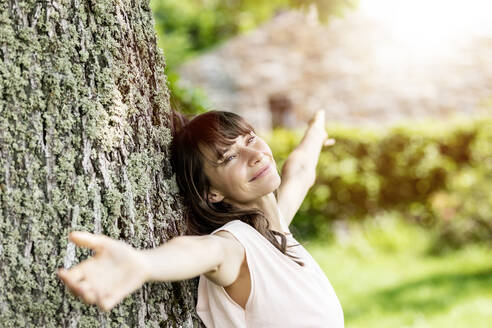 Portrait of smiling brunette woman leaning against a tree trunk - FMKF05796