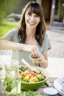 Portrait of smiling woman preparing a salad on garden table - FMKF05802
