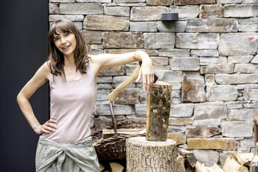 Portrait of confident woman with axe and firewood in front of a house - FMKF05814