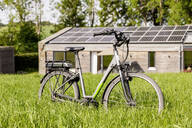 Bicycle on meadow in front of detached house - FMKF05820