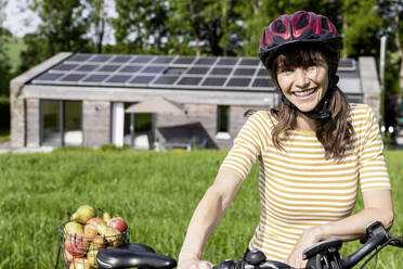 Portrait of happy woman with bicycle and organic fruit on a meadow in front of a house - FMKF05823