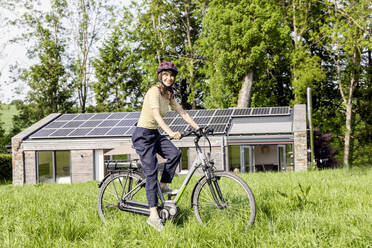 Portrait of smiling woman riding bicycle on a meadow in front of a house - FMKF05826