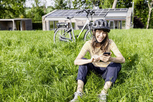 Laughing woman with bicycle using cell phone on a meadow in front of a house - FMKF05829