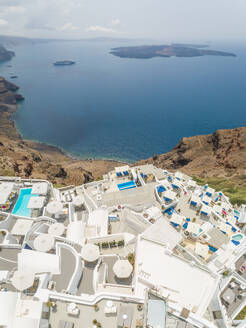 Aerial view over traditional white houses with large cruiser at sea, Santorini island, Greece - AAEF00145