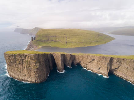 Aerial view faraway of tourists English Slave cliff on North Atlantic sea, Faroe island. - AAEF00370