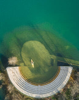 Aerial view of person kayaking next to old amphitheater at beautiful lake Plastira in Greece - AAEF00634